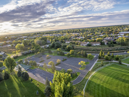aerial view of a local park with basketball courts, parking lot and baseball field in Fort Collins, Colorado, shot from a low flying drone at sunrise