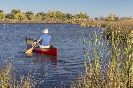 fort collins: senior male paddler paddling a red canoe on a calm lake, Riverbend Ponds Natural Area, Fort Collins, Colorado