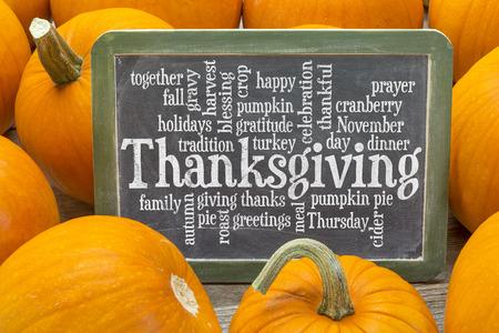 accion de gracias: nube de palabras relacionadas con la celebraci�n del D�a de Acci�n de Gracias en una pizarra pizarra rodeado de calabazas Foto de archivo
