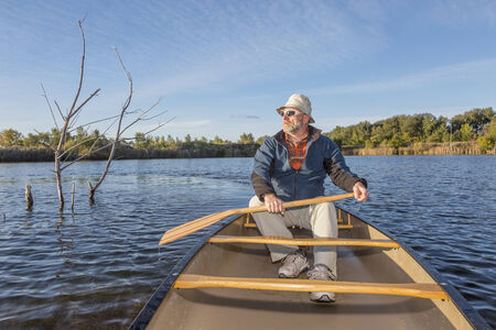 fort collins: senior paddler enjoying morning sun on lake in a canoe, Riverbend Ponds Natural Area, Fort Collins, Colorado Stock Photo