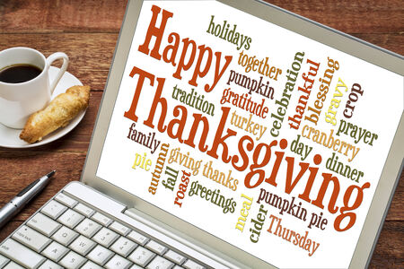 Happy Thanksgiving word cloud on a laptop with a cup of coffee - holiday concept photo