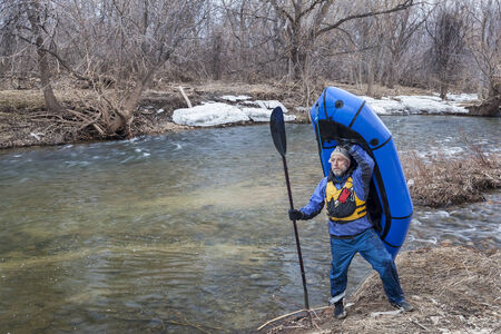 cache la poudre: senior male carrying a packraft (one-person light raft used for expedition or adventure racing) on the shore of Cache la Poudre River in Fort Collins, Colorado, winter or early spring scenery