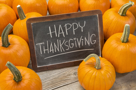 Happy Thanksgiving  - white chalk handwriting on a vintage slate  blackboard surrounded by pumpkins photo