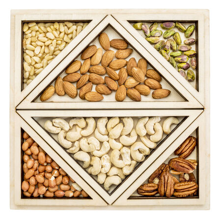 variety of nuts (almond, cashew, pecan, pine, pistachio, peanut) in a geometrical wood tray