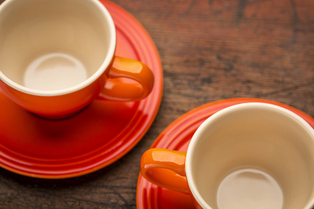stoneware: two empty stoneware coffee cups against grunge wood table, shallow depth of filed Stock Photo