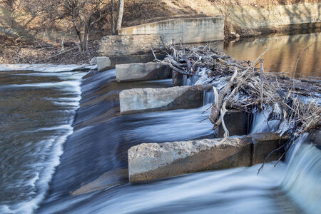 poudre river: old river dam diverting water for farmland irrigation, Cache la Poudre RIver in Fort Collins, Colorado, winter or early spring scenery Stock Photo