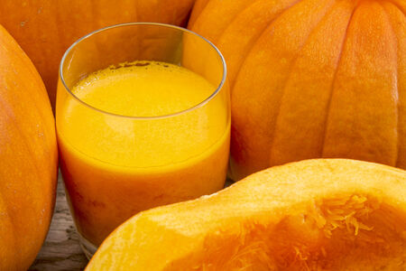 a glass of fresh pumpkin juice on a rustic wooden table surrounded by pumpkins