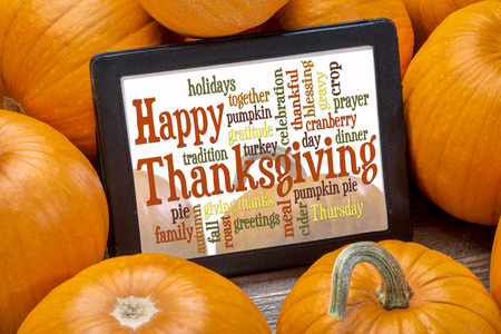 Happy Thanksgiving word cloud on a digital tablet surrounded by pumpkins photo