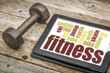 fitness word cloud on a digital tablet with a dumbbell photo