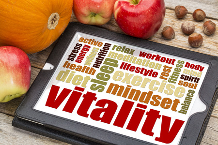 vitality or vital energy word cloud on a  digital tablet with apples, pumpkin and hazelnuts Stock Photo