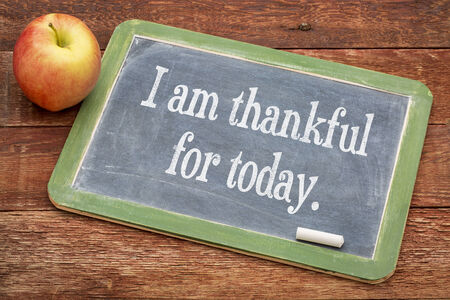 today: I am thankful for today - positive words on a slate blackboard against red barn wood