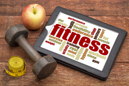 fitness word cloud on a digital tablet with a dumbbell, apple and tape measure photo