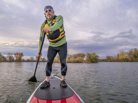 Senior Paddler in der Schwimmweste genießen Stand Up Paddling auf See, fallen Landschaft in Fort Collins, Colorado