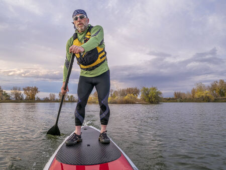 paddler: senior paddler in life jacket enjoying stand up paddling on lake, fall scenery in Fort Collins, Colorado Stock Photo