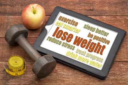 Bajar de peso - extremidades en una tableta digital con una pesa de gimnasia, manzana y cinta métrica Foto de archivo - 32923609