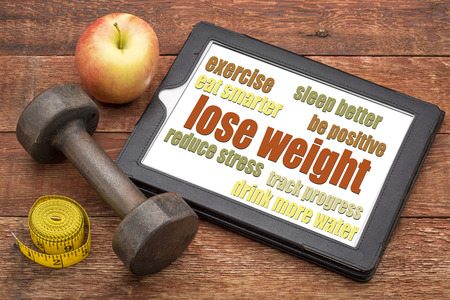lose: lose weight - tips on a digital tablet with a dumbbell, apple and tape measure