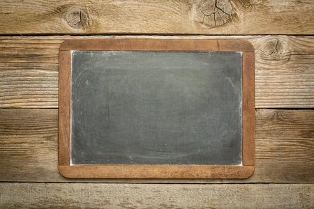 blank slate blackboard against rustic weathered wood planks photo