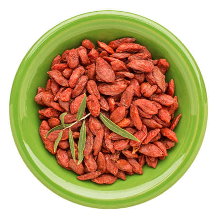 dried goji berries with a fresh leaf on an isolated green ceramic bowl photo