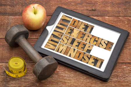sleep well: diet, sleep, exercise and mindset - vitality concept - abstract in vintage letterpress wood type on a digital tablet with a dumbbell, apple and tape measure