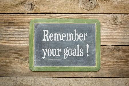 recordar: recordar su recordatorio metas sobre una pizarra pizarra en contra de los tablones de madera resistidos rústicos Foto de archivo