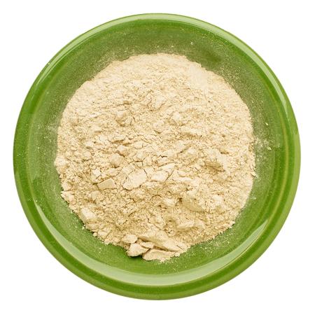 maca: maca en polvo de la ra�z en un taz�n de cer�mica verde aislado
