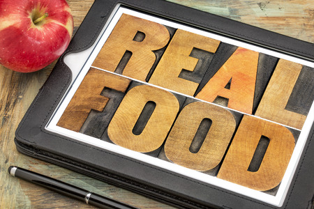 unprocessed: healthy lifestyle concept - real food, text in vintage letterpress wood type on a digital tablet with a fresh apple Stock Photo