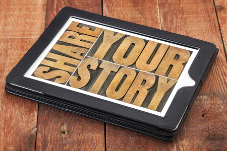 share your story word abstract  - isolated text in vintage letterpress wood type on a digital tablet against rustic red barn wood Stock fotó