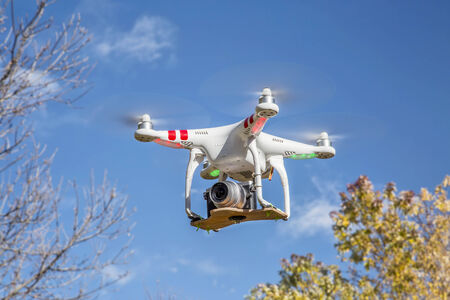 airborne: FORT COLLINS, CO, USA, November 2, 2014:  Airborne radio controlled Phantom 2 quadcopter drone flying over trees with  the Panasonic Lumix GM1 camera mounted on a home made platform.