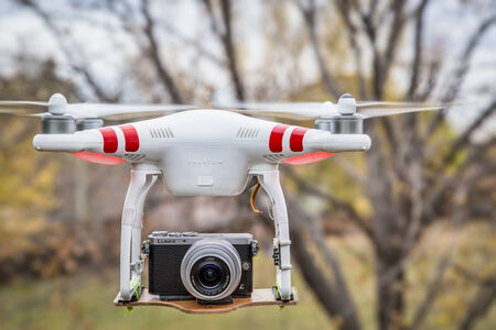 2 november: FORT COLLINS, CO, USA, November 2, 2014:  Airborne radio controlled Phantom 2 quadcopter drone flying with  the Panasonic Lumix GM1 camera mounted on a home made platform, blurred tree background. Editorial