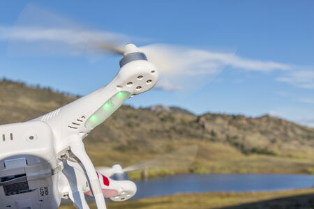 FORT COLLINS, CO, USA, September 30 2014:  Airborne radio controlled DJI Phantom quadcopter drone is flying over Pineridge Natural Area at Colorado foothills.