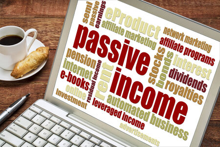 passive income: passive income word cloud  on a laptop with a cup of coffee