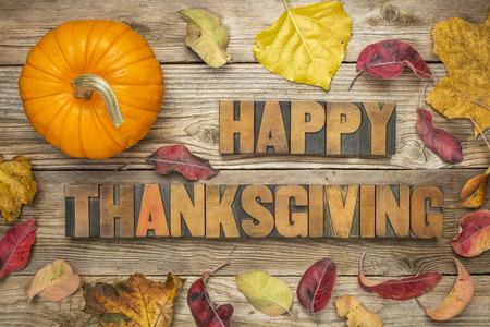 animados: Feliz Acción de Gracias - texto en tipografía de época bloques de tipo de madera contra el fondo de madera rústica con una calabaza y hojas secas