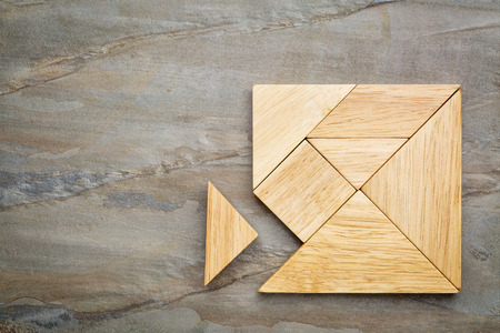red puzzle piece: a missing piece in a square built from tangram pieces, a traditional Chinese puzzle game, slate rock background