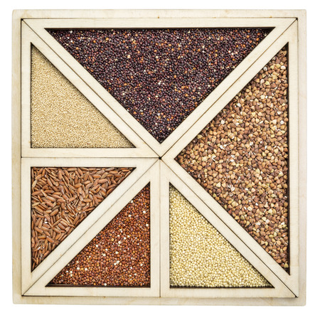 variety of gluten free grains (red and black quinoa, buckwheat, brown rive, amaranth and millet) in a wooden tray Stockfoto