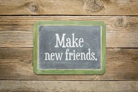 make new friends reminder on a  slate blackboard against rustic weathered wood planks