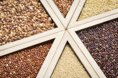 variety of gluten free grains (red and black quinoa, buckwheat, brown rive, amaranth and millet) in a wooden tray, focus on quinoa and amaranth Stockfoto