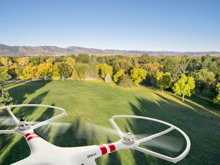 drone: drone flying over park in fall colors under morning light with deep long shadows Stock Photo