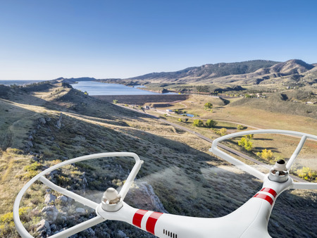 quadcopter drone flying over mountain valley and reservoir