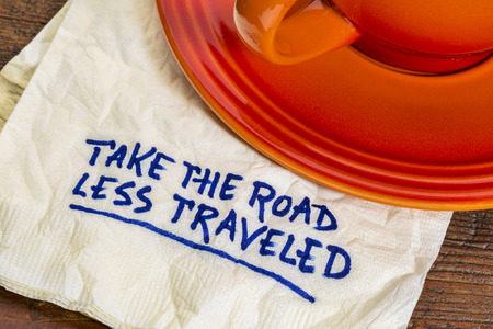 traveled: take the road less traveled - handwriting on  a napkin with a cup of coffee
