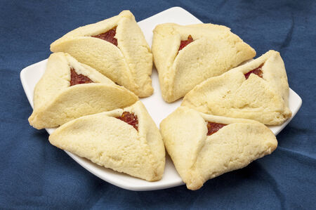 hamantasch: apricot hamantaschen cookies  on a plate against blue tablecloth - a traditional pastry in Ashkenazi Jewish cuisine for holiday of Purim Stock Photo