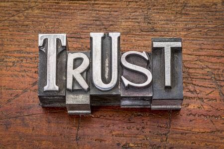 trust: trust word in vintage metal type printing blocks over grunge wood
