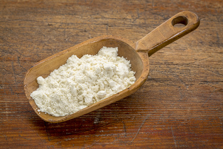 protein: rustic scoop of whey protein powder against grunge wood table