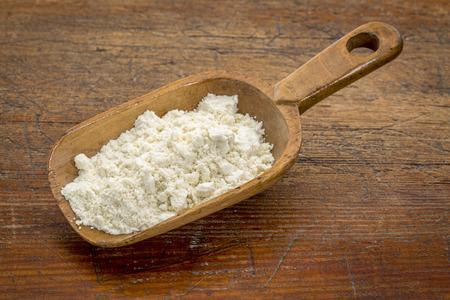 Rustico scoop di proteine ??del siero di latte in polvere contro il grunge tavolo in legno Archivio Fotografico - 33702944