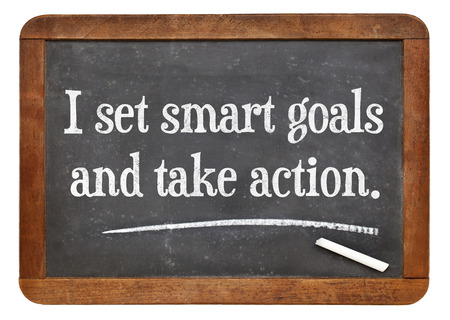 setting goals: I set smart goals and take action - positive affirmation words on a vintage slate blackboard