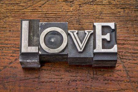 love word in vintage metal type printing blocks over grunge wood photo