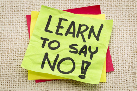 learn to say no advice or reminder on a green sticky note against burlap canvas