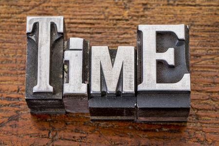 time word in vintage metal type printing blocks over grunge wood photo