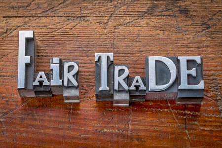 wood trade: fair trade words in vintage metal type printing blocks over grunge wood - ethical business concept