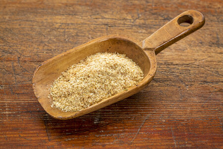 flax seed: rustic scoop of golden flax seed meal against grunge wood table Stock Photo