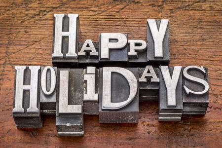 Happy Holidays greetings  in vintage metal type printing blocks over grunge wood photo